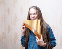 Long-haired Elderly Man With Pan Flute Royalty Free Stock Image