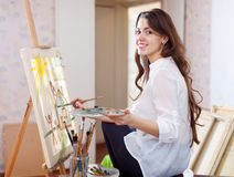 Long-haired female artist paints picture on canvas. With oil paints in her stidio royalty free stock image