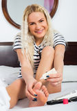 Long haired female taking care of toes and feet. Indoors Stock Photo