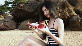 Long-haired girl on the beach demonstrates the flesh of the dragon fruit exotic. stock footage