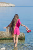 Long-haired girl on the beach. Young woman in red comes into water Royalty Free Stock Photos
