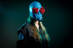 Long haired girl in a blue gas mask. With red flower eyes. Dark green background stock photo