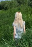 Long-haired girl bush grass. Stock Photos