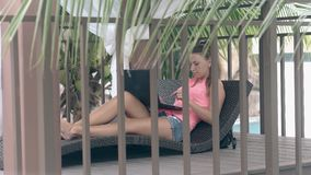 Girl lies on sunbed behind metal fence and works on laptop. Long haired girl in denim shorts lies on wicker sunbed in arbor behind metal fence near palm leaves stock footage