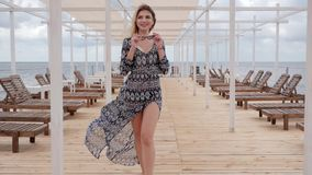 Long-haired girl in developing clothes on waterfront, young woman in glasses walks on wooden pier, expensive holidays stock video footage