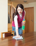 Long-haired girl  dusting table Stock Photo
