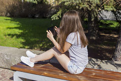 Long haired girl enjoys the tablet on bench Royalty Free Stock Images