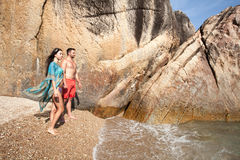 Long-haired girl and guy near large stone and sea. Royalty Free Stock Images