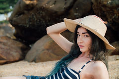 Long haired girl In a hipster hat and striped swimsuit relax on tropical beach, background of stones. Stock Images