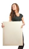 Long haired girl in holds an empty poster. Long-haired girl holds an empty poster. Isolated on white Royalty Free Stock Photo