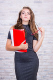 Long-haired girl imitates  office administrator with red folder Stock Image