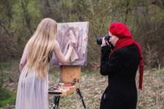 Long-haired girl in the lens of the camera artist paints in oils on canvas self portrait. Easel outdoors. The girl photographer photographing the artist in the stock photo