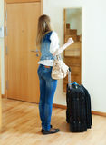 Long-haired girl with luggage looking in mirror. Near door in home Royalty Free Stock Photo