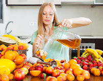 Long-haired girl making fresh beverages Stock Images