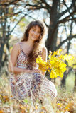 Long-haired girl with oak posy. Outdoor portrait of long-haired girl with oak posy in autumn Royalty Free Stock Images