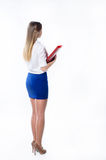 Long-haired girl in the office clothes standing back Royalty Free Stock Image