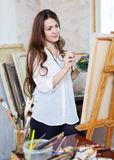 Long-haired girl paints on easel Royalty Free Stock Images
