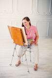 Long-haired girl paints with oil colors on easel Royalty Free Stock Photos