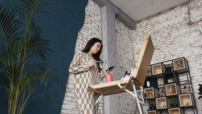 Long-haired girl paints with palette shades on easel in workshop interior. Beautiful brunette woman painter paints on. Waterproof paper using board easel. Loft stock footage