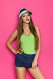 Long-Haired Girl Posing In Sun Visor. Smiling young beautiful woman in jeans shorts and lime green shirt posing in green sun visor cap and holding hand on hip Royalty Free Stock Photos