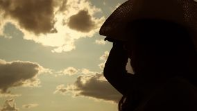 Long haired girl silhouette puts on cowboy hat close view