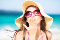 Long haired girl in straw hat blowing a kiss on Royalty Free Stock Photo