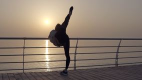Long haired girl stretches her leg with a view of the sea ocean. Dawn Sunrise. Sportswear, leggings, hoodies. Dusk.  stock video footage