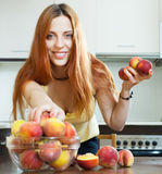 Long-haired girl taking peaches Stock Photo