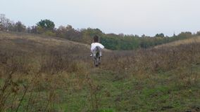 Long-haired girl in wedding dress riding galloping horse through field