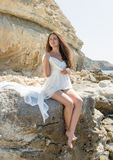 Long-haired girl in wedding dress sitting on stone barefoot. Dark-haired young woman in white sleeveless dress sits on coastal rock in the backlighting royalty free stock image