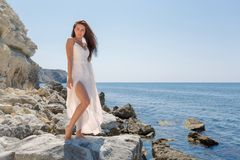 Long-haired girl in wedding dress standing on stone barefoot. Dark-haired young woman in white sleeveless dress posing on coastal. Rock in the backlighting royalty free stock photo