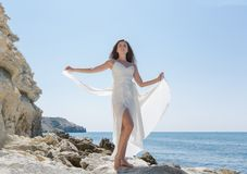 Long-haired girl in wedding dress standing on stone barefoot. Dark-haired young woman in white sleeveless dress poses arms outstretched on coastal rock royalty free stock images