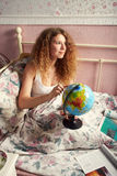 The long-haired girl in a white undershirt, sitting on a bed. Something looks for on the globe and smiles to the dreams stock photo