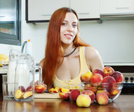 Long-haired girl in yellow cooking with peaches Stock Photos