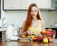Long-haired girl in yellow  with peaches at home Royalty Free Stock Photo