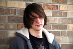 Long Haired Hippie. Cute teen boy smiling with great hair by brick wall Stock Image