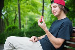 A long-haired hipster in a cap sits on a bench and spins a fidget-spinner Stock Photos