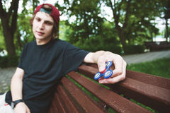 A long-haired hipster in a cap sits on a bench and spins a fidget-spinner Stock Photography