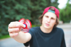 A long-haired hipster in a cap sits on a bench and spins a fidget-spinner Royalty Free Stock Photography