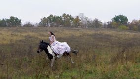 Long-haired horsewoman in wedding dress riding galloping horse along field