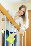 Long-haired housewife cleaning stair railings with rag Royalty Free Stock Photo