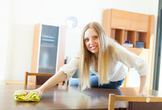Long-haired housewife cleaning table with rag Stock Images