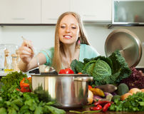 Long-haired housewife cooking  at home kitchen Royalty Free Stock Photography