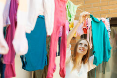 Long-haired housewife hanging clothes to dry Royalty Free Stock Photo