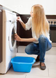 Long-haired huosewife doing laundry Royalty Free Stock Photo