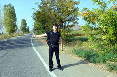 Long haired male hitchhiker. With backpack catches car on the sidelines Royalty Free Stock Photo