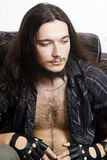 Long haired man with a hairy chest in the chair Stock Photos