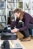 Long haired man putting an lp record on the turntable Royalty Free Stock Photography