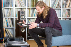 Long haired man putting a vinyl on the turntable. Long haired man looking at the track list on a vinyl long playing record to put on the turntable Royalty Free Stock Photo