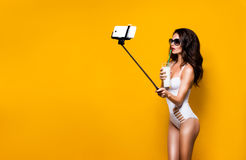 Long-haired model in white monokini making seflie with selfie stick. Stock Photos